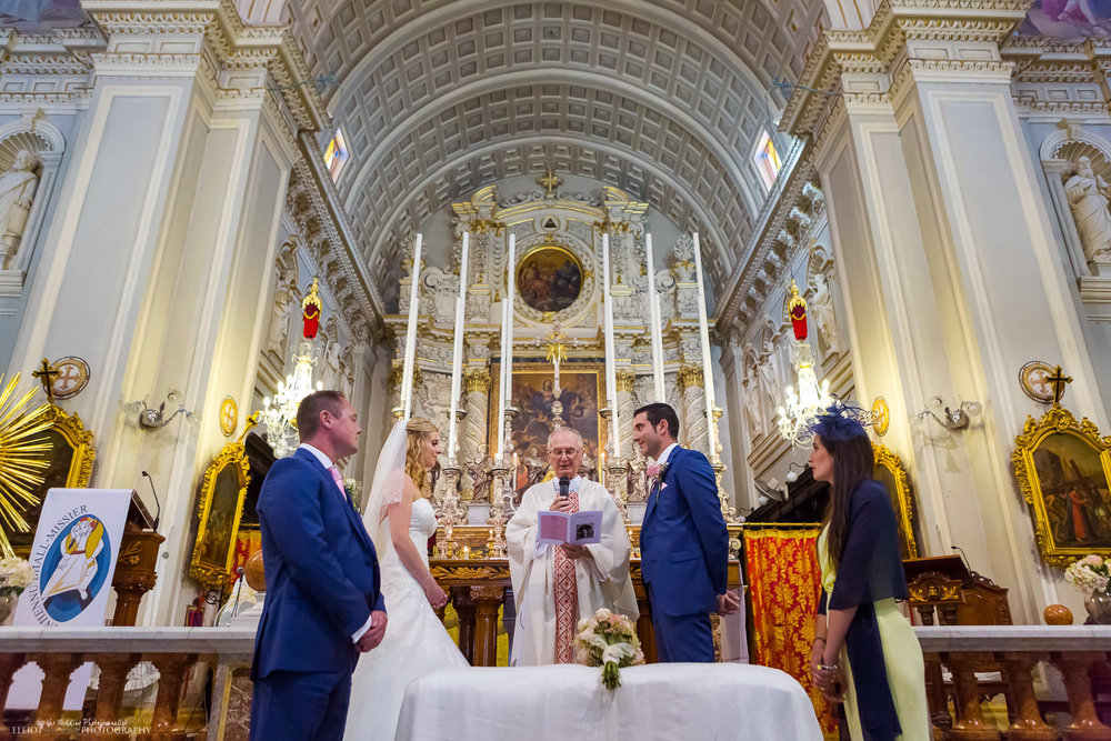 Bride and Groom at the altar with the priest during the wedding ceremony in Malta