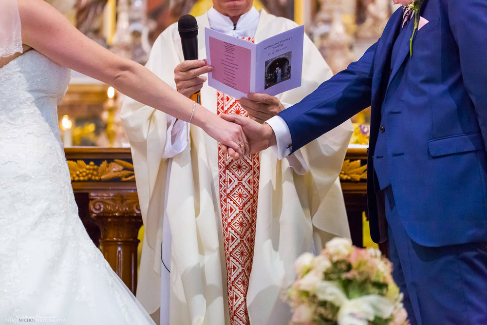 Bride & groom hold hands while they say their wedding vows