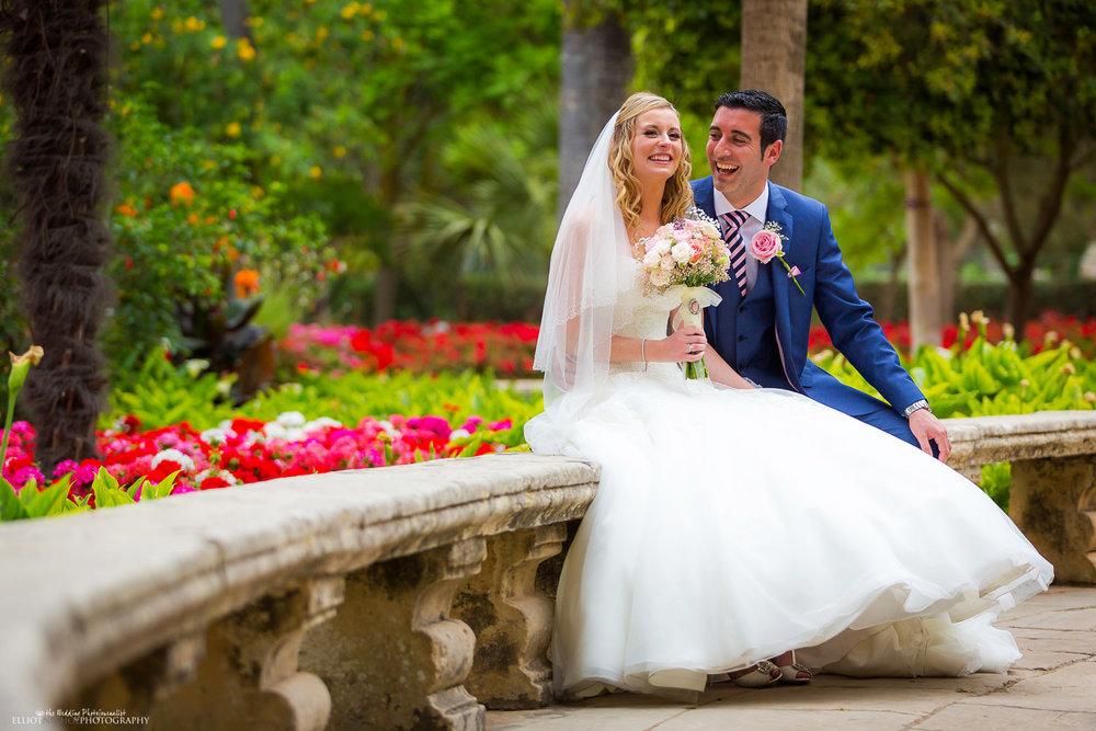 Portrait of bride and groom sitting in San Anton Gardens in Attard
