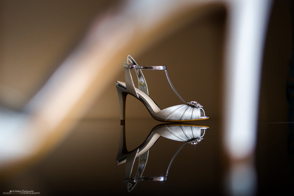 brides wedding shoe placed on a reflective table