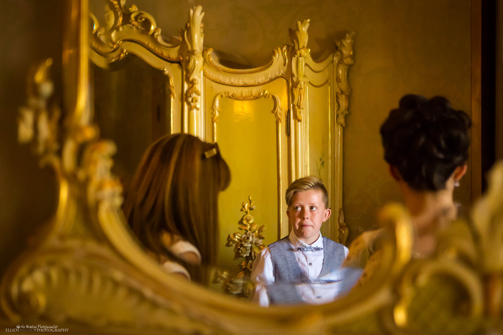 Nervous pageboy's reflection in a gold mirror in the Bridal suite in the Palazzo Parisio, Naxxar, Malta