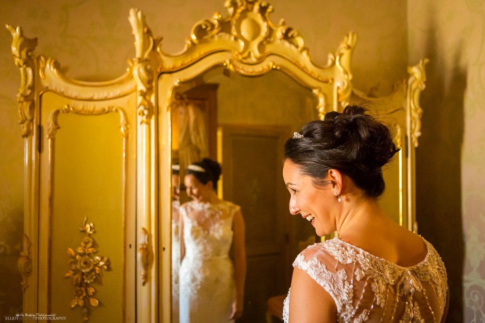 Bride looking at her reflection in a golden wardrobe in the Parisio's bridal suite