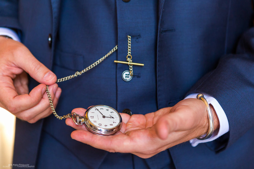 groom looking at the time on his pocket watch while waiting for the wedding ceremony to begin