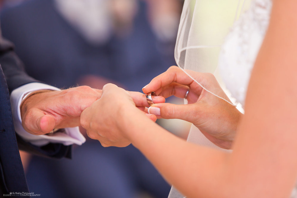Bride puts wedding band onto grooms wedding finger.