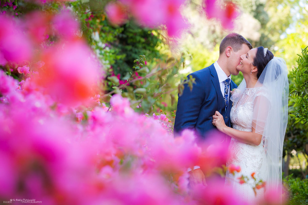 Portrait of the bride and groom surrounded by pink flowers in the Palazzo Parisio Gardens.