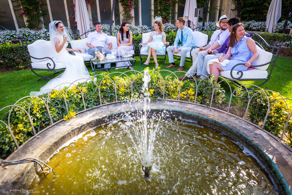 Bride sits with the wedding guests around a water fountain.