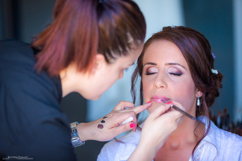 Bride getting her makeup applied by the makeup artist