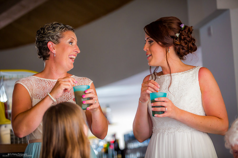 Bride laughing with her bridesmaid over a drink at the Seabank hotel