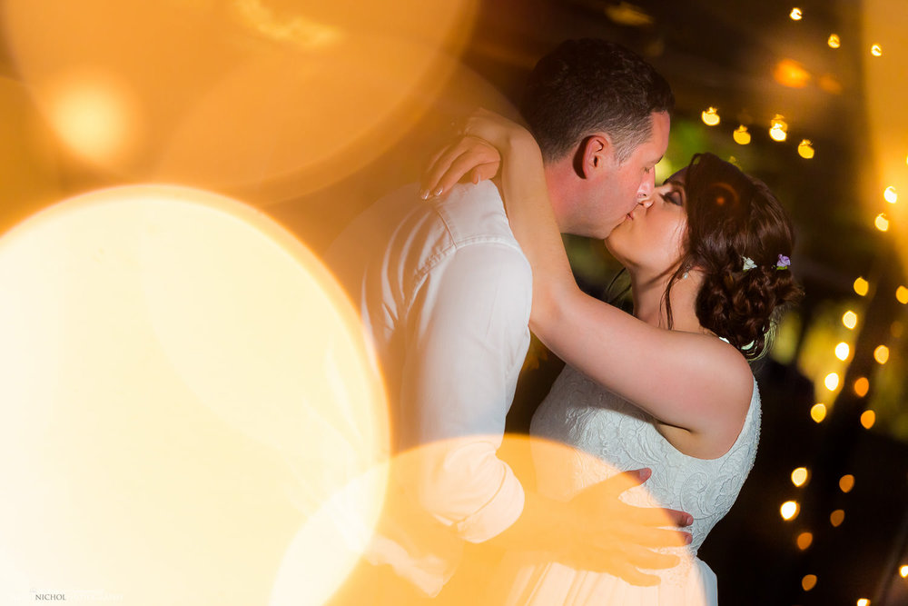 Bride and Groom kissing surrounded by fairy lights at the Seabank Resort, Mellieha, malta
