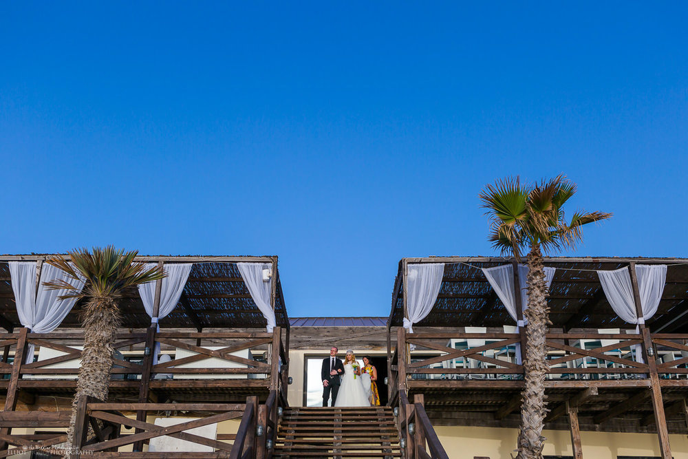 Bride arrives at the wedding ceremony with her brother at the steps of the Amazonia Terrace at the Dolmen Hotel, Malta.