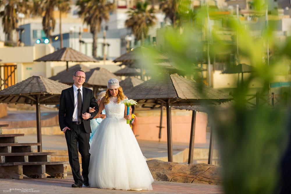 Bride walks towards the wedding ceremony on the Amazonia Lower deck at the Dolmen Resort Hotel, Qawra, Malta.