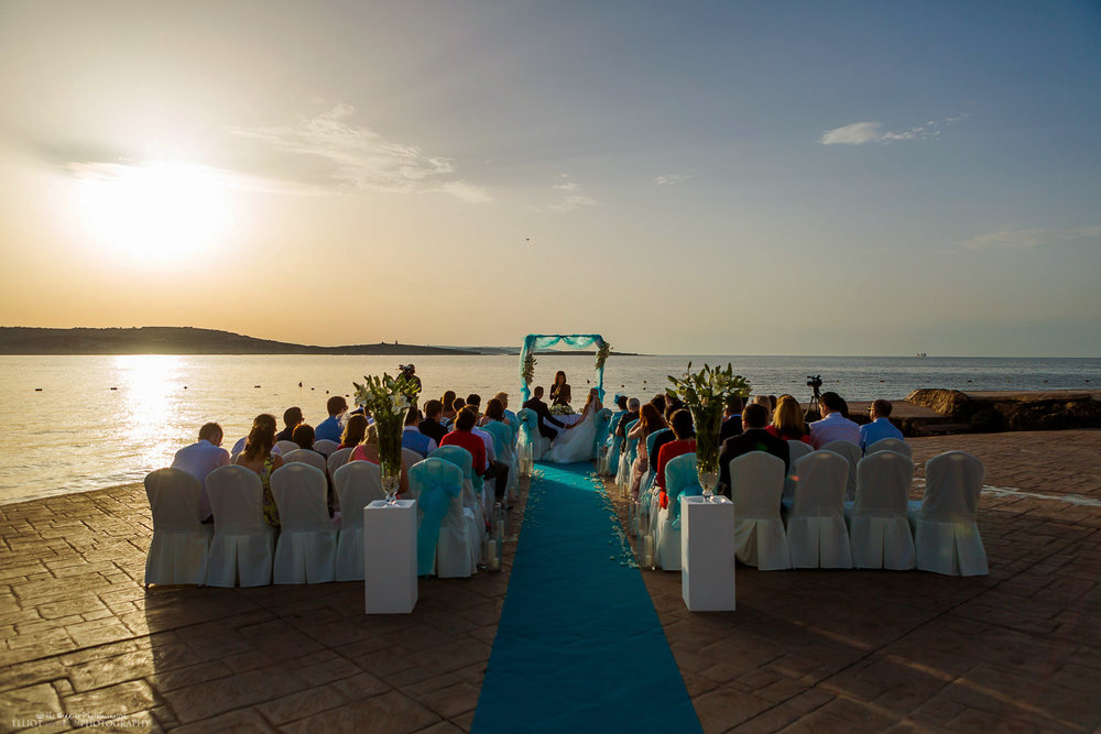 Sunset wedding ceremony by the sea in Malta at the Dolmen Resort at St Paul's Bay.