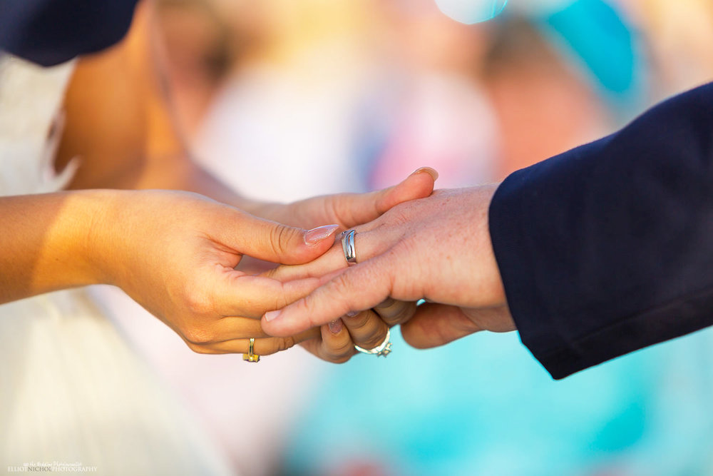 Bride places wedding ring on grooms finger during the wedding blessing