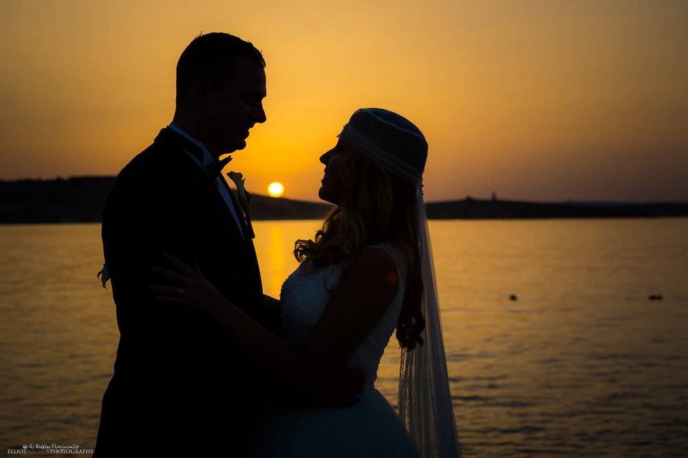 Silhouette of the Bride and Groom during sunset by the Mediterranean sea in Malta.