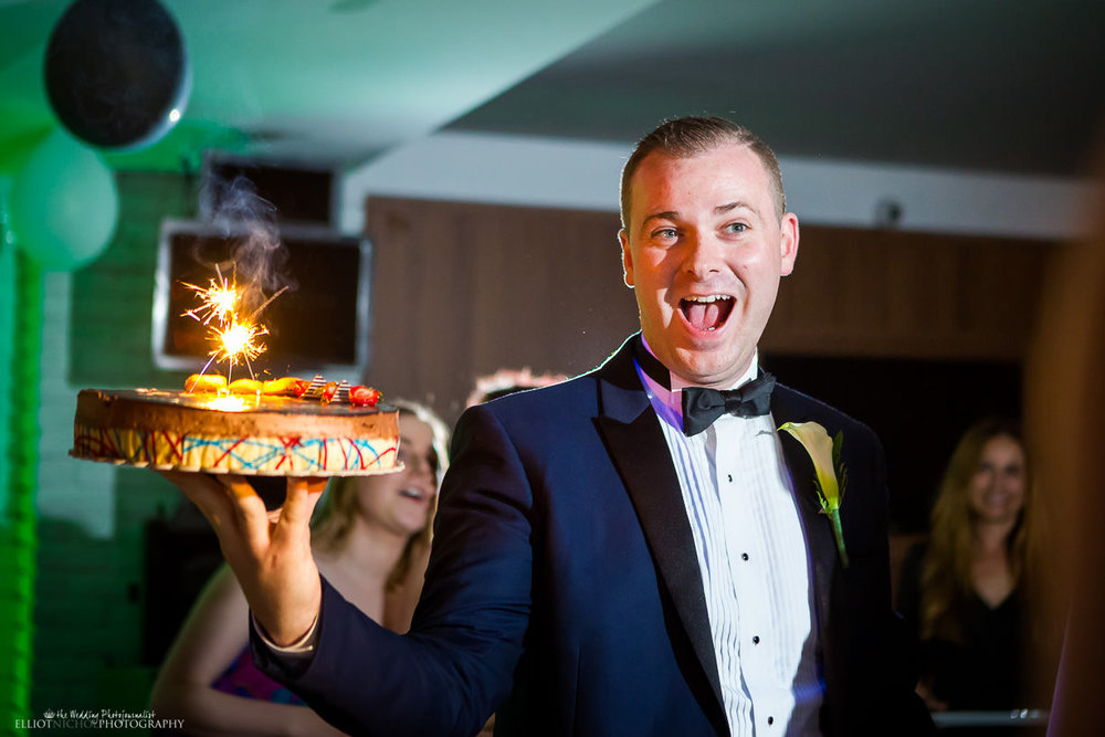 Groom with a birthday cake for one of his wedding guests
