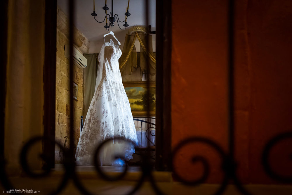 wedding dress hanging from a chandelier in the brides bedroom.