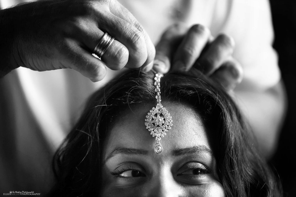 Brides wedding day hair jewellery being fixed but her hair stylist.