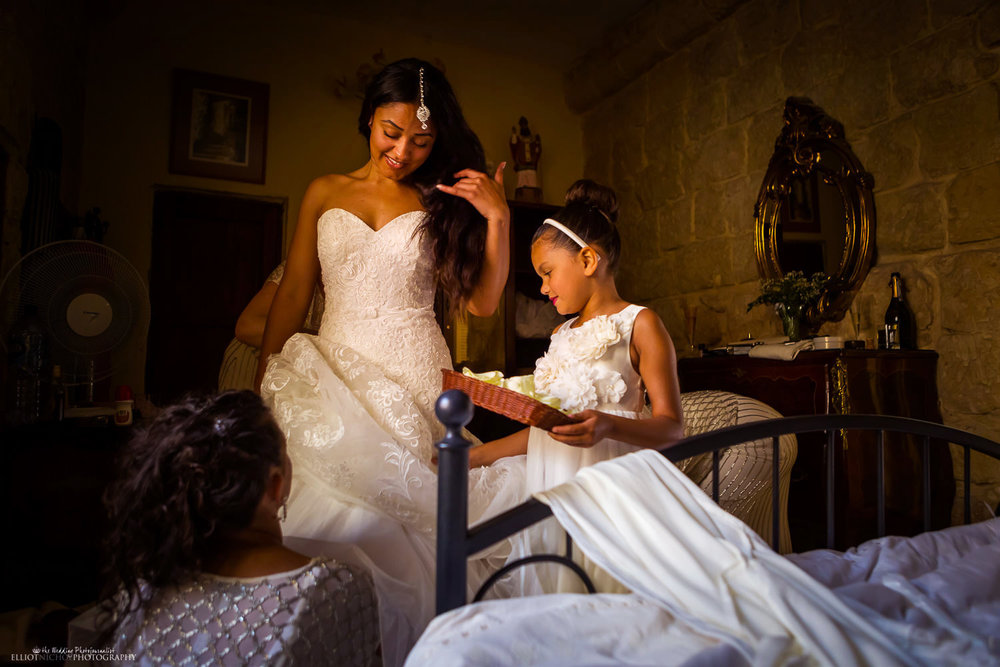Bride getting into her wedding dress helped by their bridesmaids and flower girl.