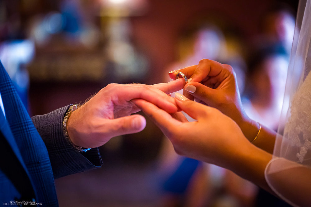 Bride places ring on grooms wedding finger.