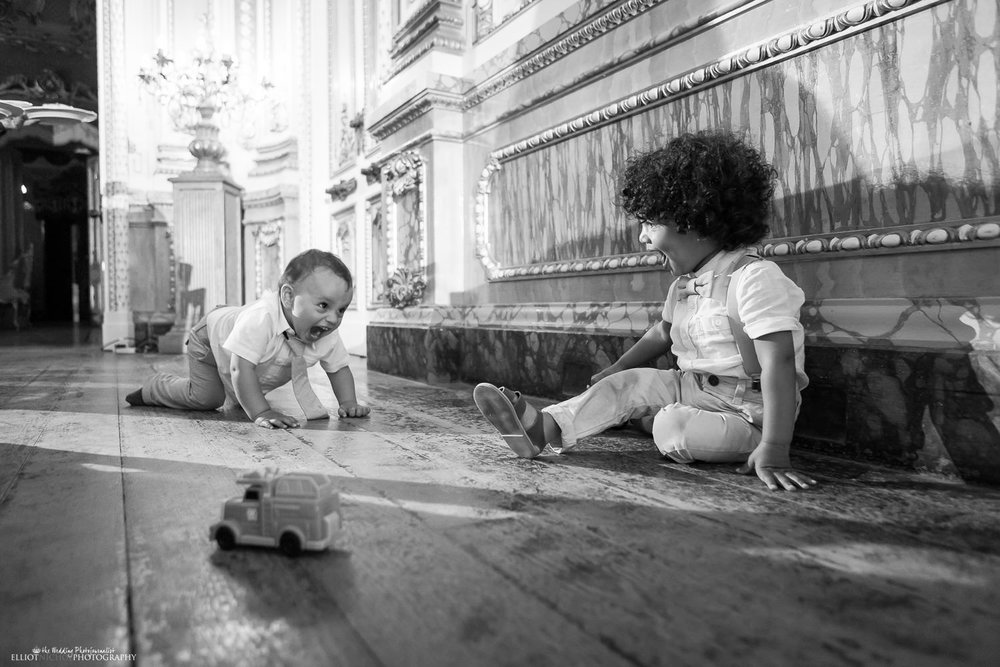 To young wedding guests playing on the Palazzo Parisio's ballroom's wooden floor.