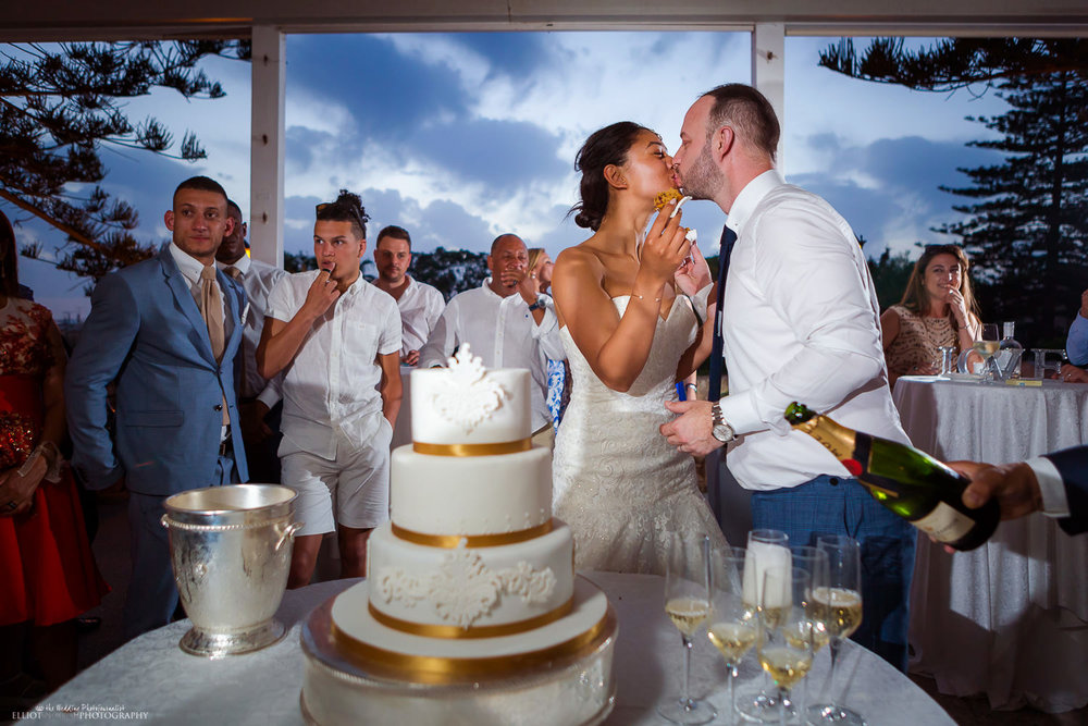 Bride and groom kiss after cutting their wedding cake on the Balcony Terrace at the palazzzo Parisio in Malta.