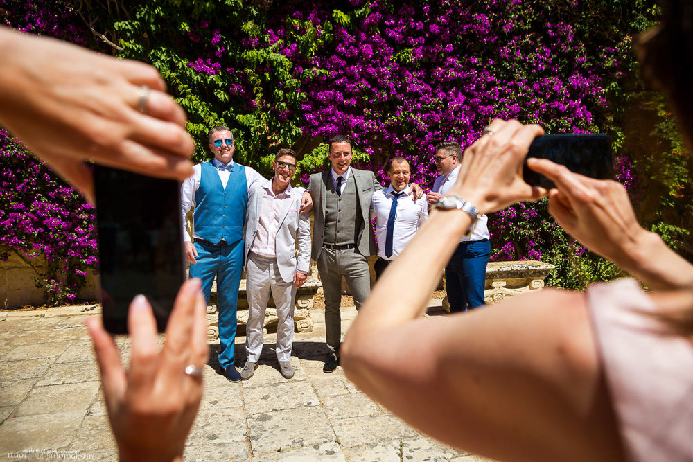 Joanna & Pauls's wedding guests taking photo's of each other in front the Villa Bologna's Baroque Garden flowered garden wall.