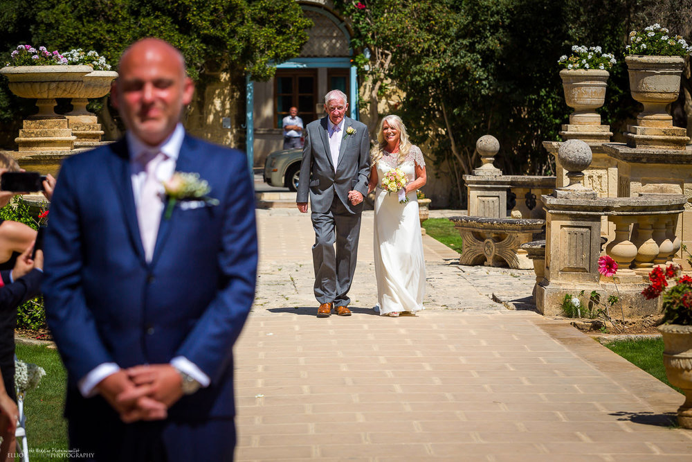 Bride and her father arrive and walk towards the wedding ceremony in the Baroque Gardens of the Villa Bologna, Malta.