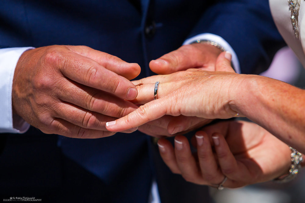 Groom places ring on his brides wedding finger