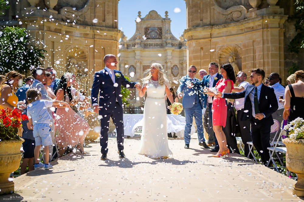 Newlyweds walk through a shower of confetti in the Baroque Gardens at the wedding venue Villa Bologna, Malta