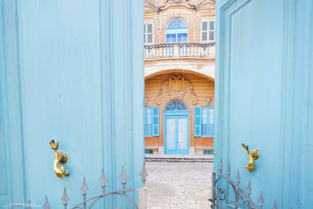 Blue front doors open showing the front facade of Villa Bologna, Malta.