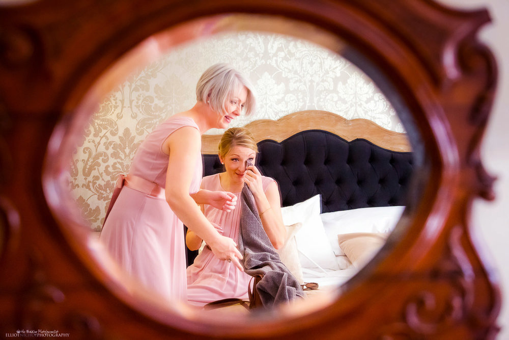 Emotional bridesmaid reflected in mirror after she saw the bride in her wedding dress.