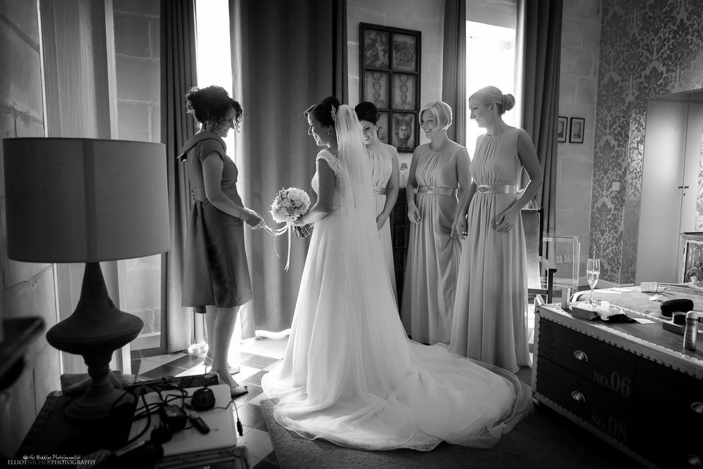 Bride with her mother surrounded by her bridesmaids just before they leave to go to the wedding ceremony in Mdina, Malta