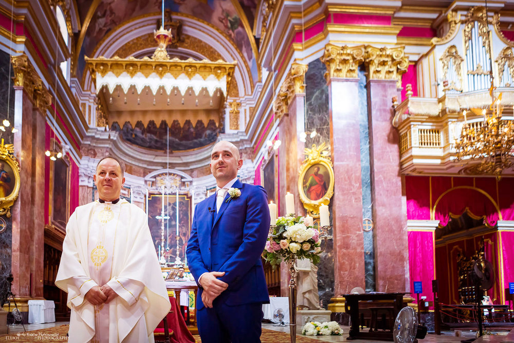 Groom standing with priest in Mdina Cathedral, Malta.