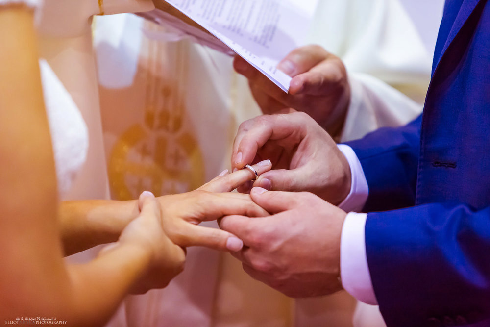 Groom puts wedding ring on his bride during the wedding ceremony