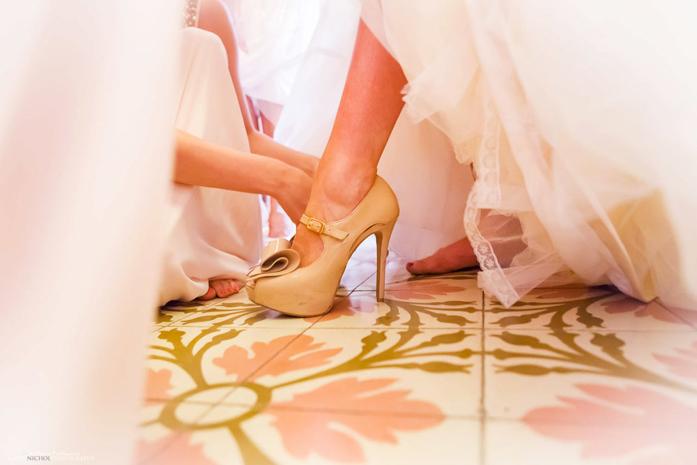 Bride having her shoes put on by her bridesmaids