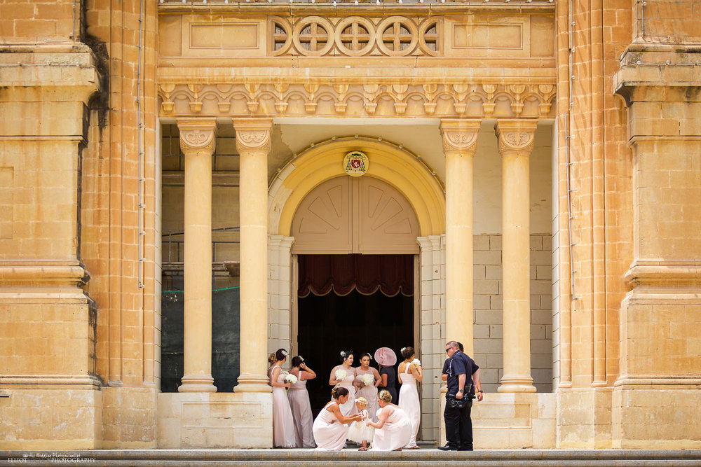 Bridesmaids and flower girl arrive outside St Peter's Parish Church in Birzebbuga, Malta.