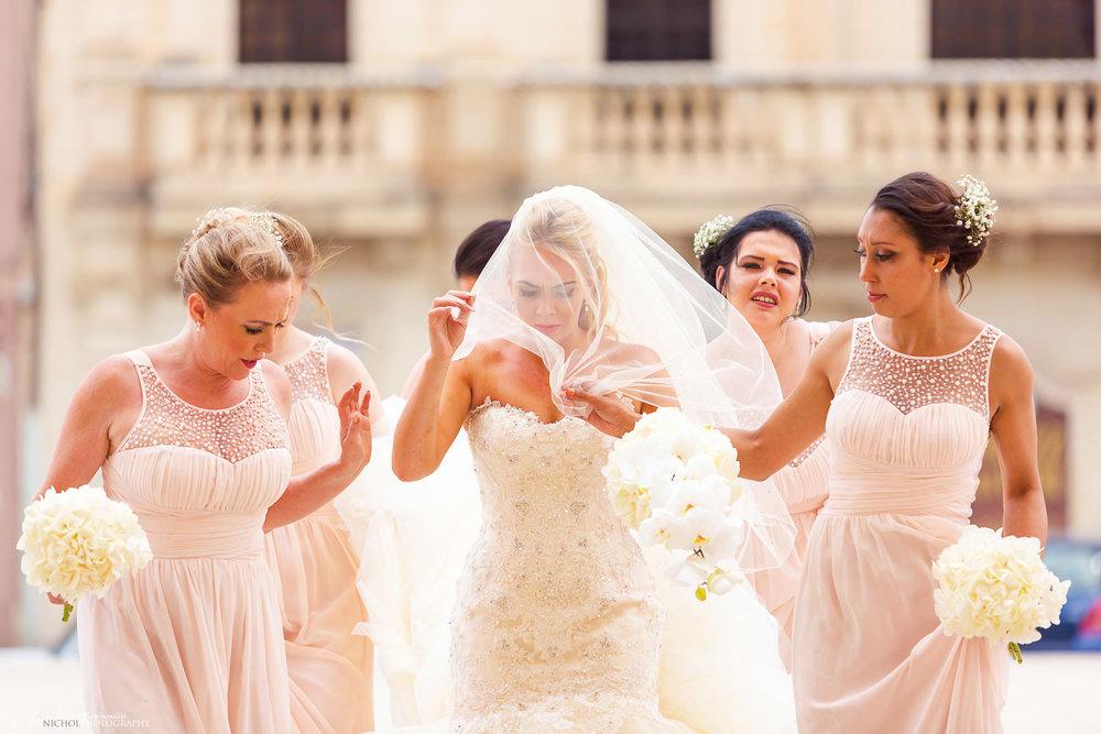 bride walks to the church under her veil
