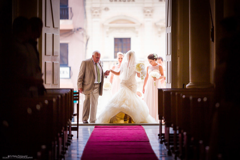 Bride enters the Parish Church of St Peter in Birzebbuga, Malta with her father and bridesmaids.