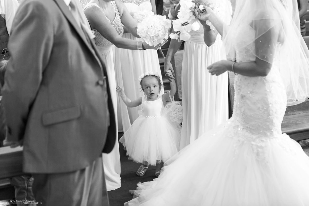 Flower girl in the wedding procession arrives at the altar
