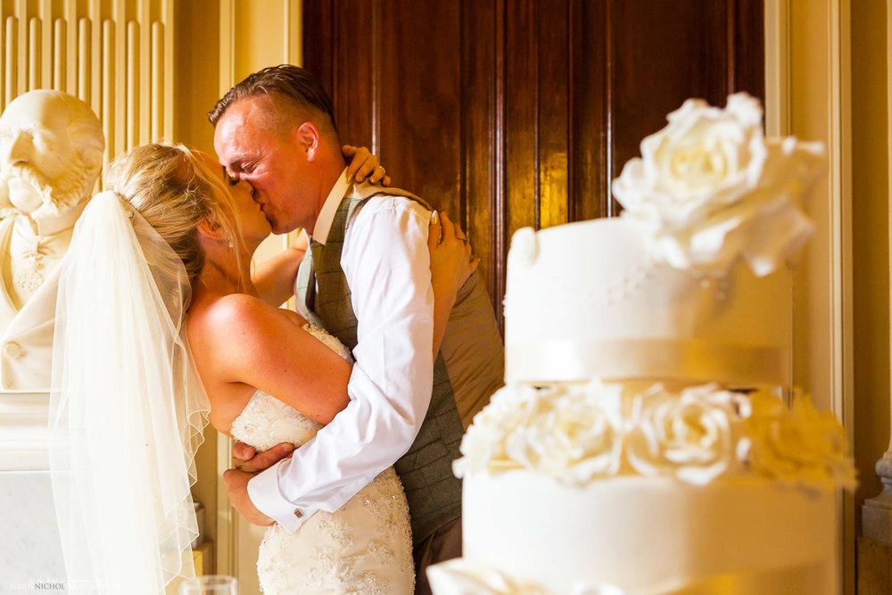 newlyweds kissing my the wedding cake