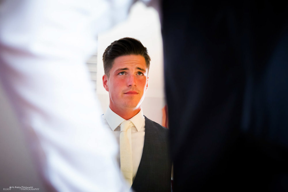 groom thoughtfully looks in the mirror as he gets ready for his wedding.