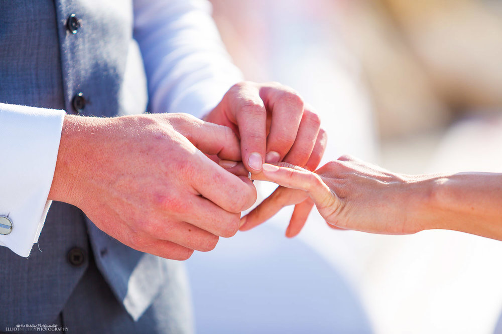 Groom puts wedding ring onto his brides wedding finger