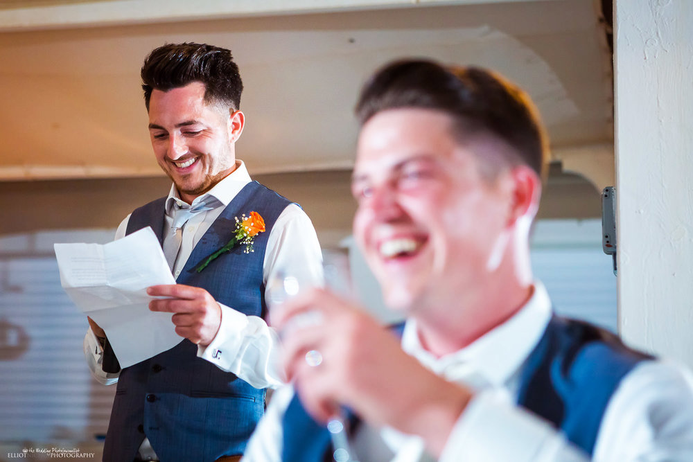 Groom laughing at his best man's wedding speech during the wedding reception