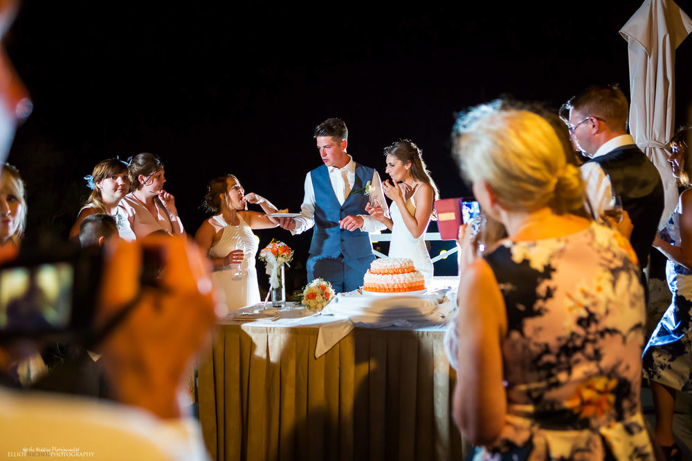 Bride and groom sharing their wedding cake out to their wedding guests