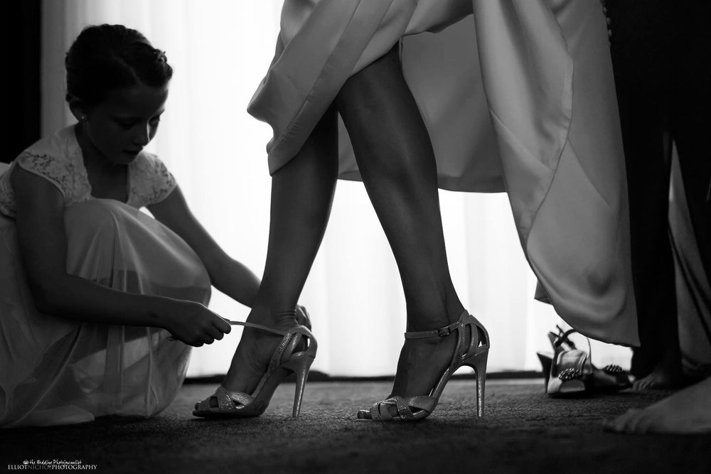 Flower girl helps the Bride put on her wedding shoes for her destination wedding in Malta.