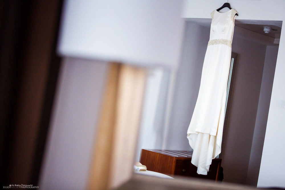 Brides wedding dress hanging in her hotel room at the Radisson Blu Resort, St Julians, Malta