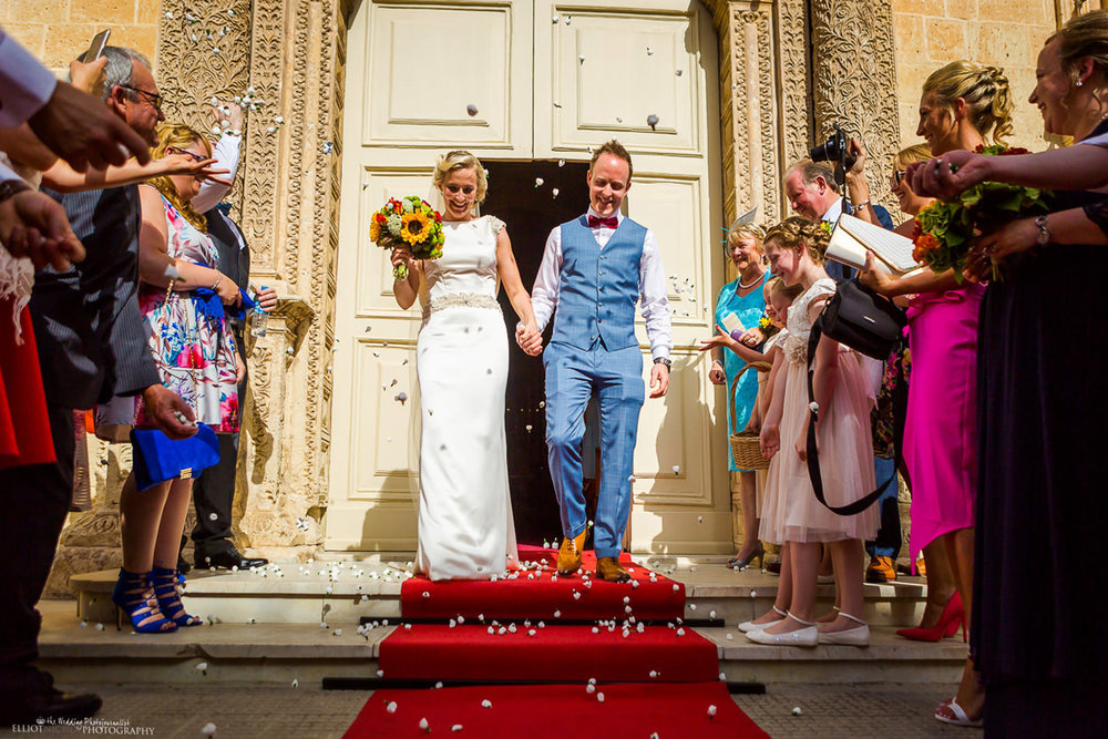 Newlyweds leave the church under a shower of confetti