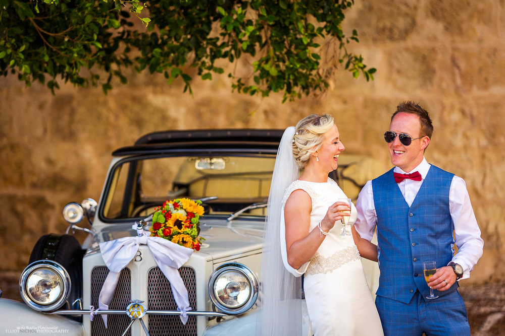 Bride and groom drink champagne next to their vintage wedding car