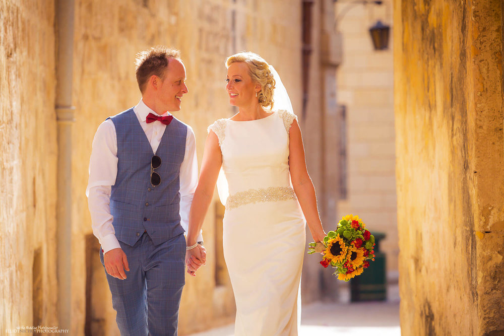 Newlyweds walking through the streets of Mdina, Malta.