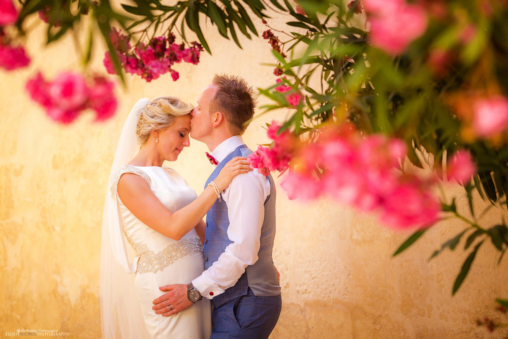 Destination Bride & groom portrait under a flowering tree in Mdina, Malta